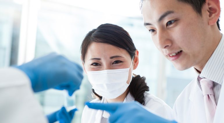 Technicians viewing a vial