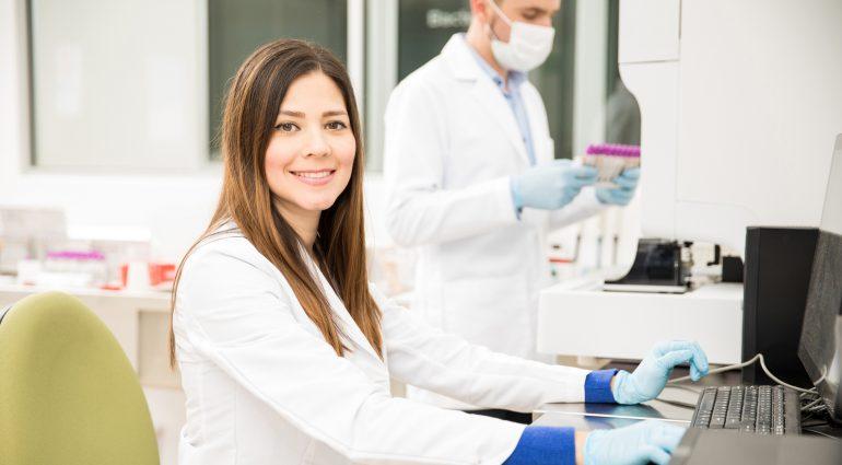 Laboratory technician at terminal, smiling at camera